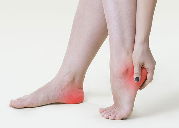 Woman grasping heel due to heel pain